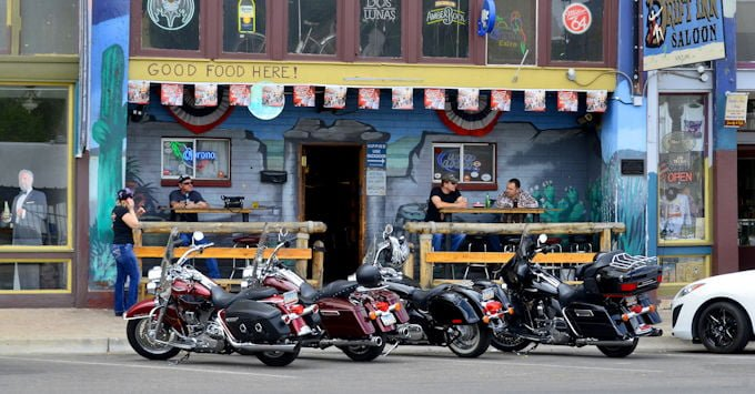 Row of Harley Davidson motorcycles parked in front of a bar